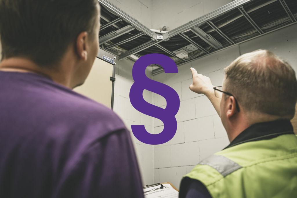Kata Safetyn Janne ja Joni Rahunen tarkastamassa kiinteistön palokatkoja. Kuvassa kaapelihylly ja keskelle liitetty lakipykälä-symboli